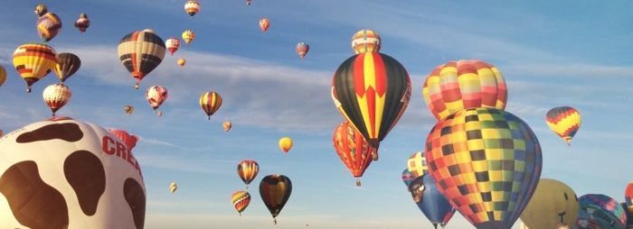 colorful hot air balloons floating through a blue sky
