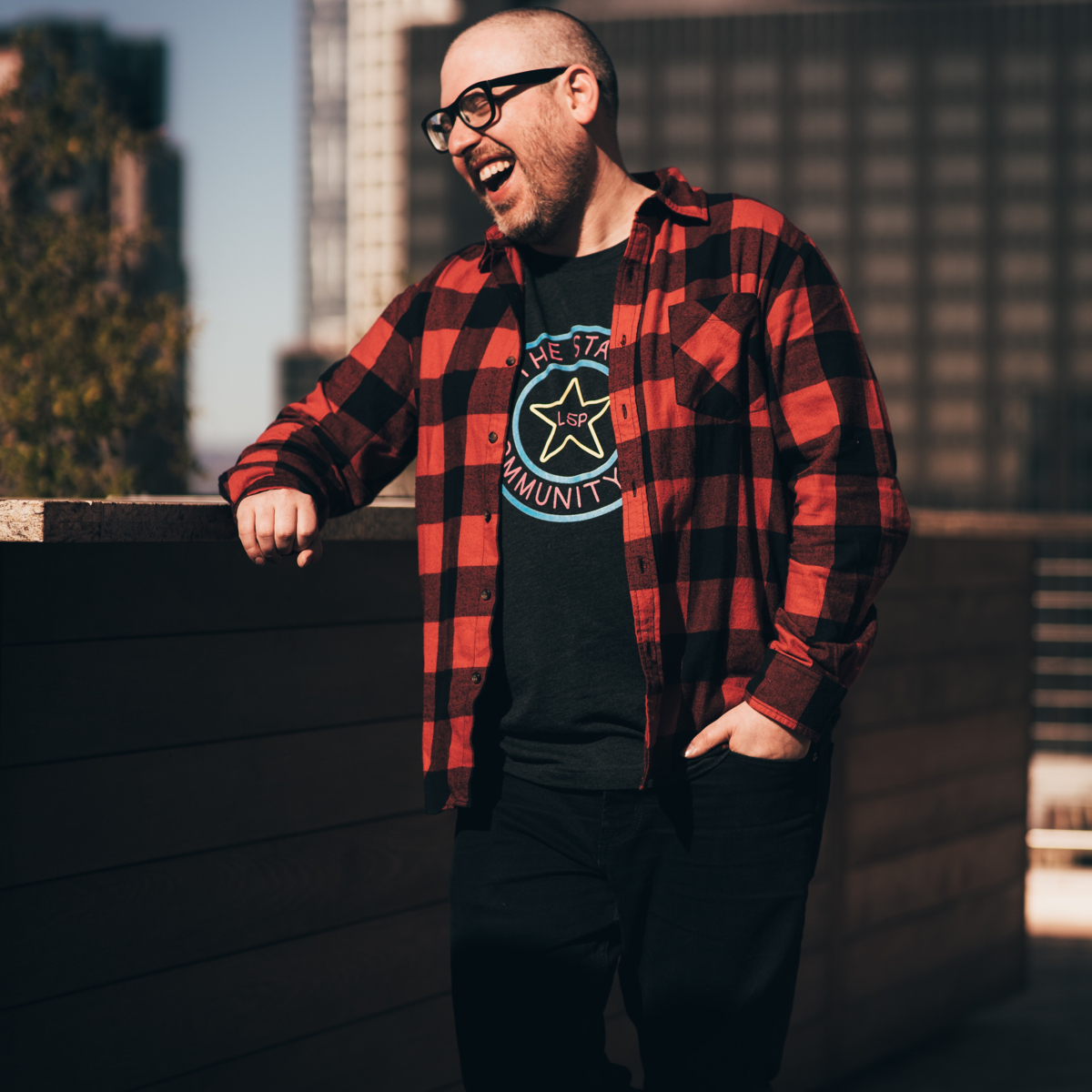 Justin Morgan leaning on a wall, laughing, and wearing red plaid