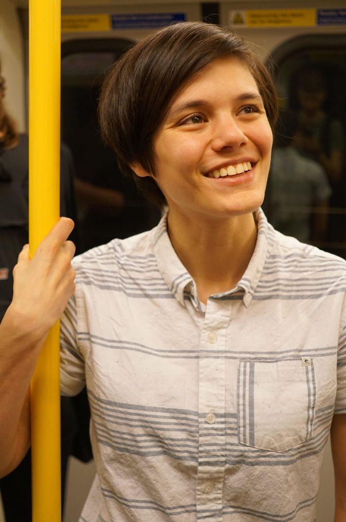 Eleanor Lewis gripping a subway pole.