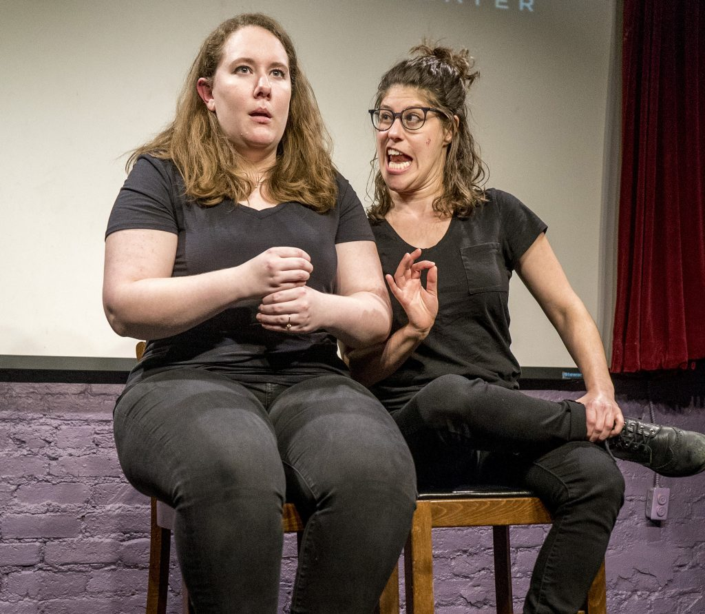 Elena Skopetos and Elana Fishbein seated onstage performing a scene.